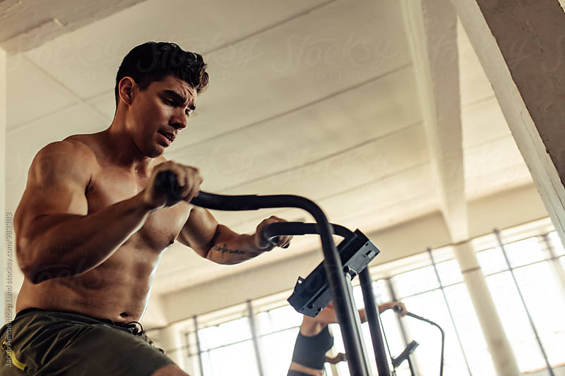 Muscular man working out on the exercise bike at the gym by Jacob Lund for Stocksy United