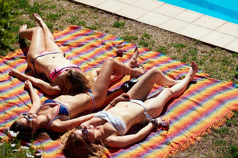 Friends in bikini sunbathing on colorful blanket by Guille Faingold for Stocksy United
