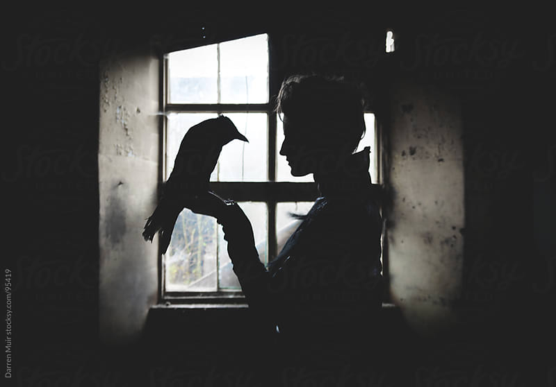 Woman with her pet crow.  by Darren Muir for Stocksy United