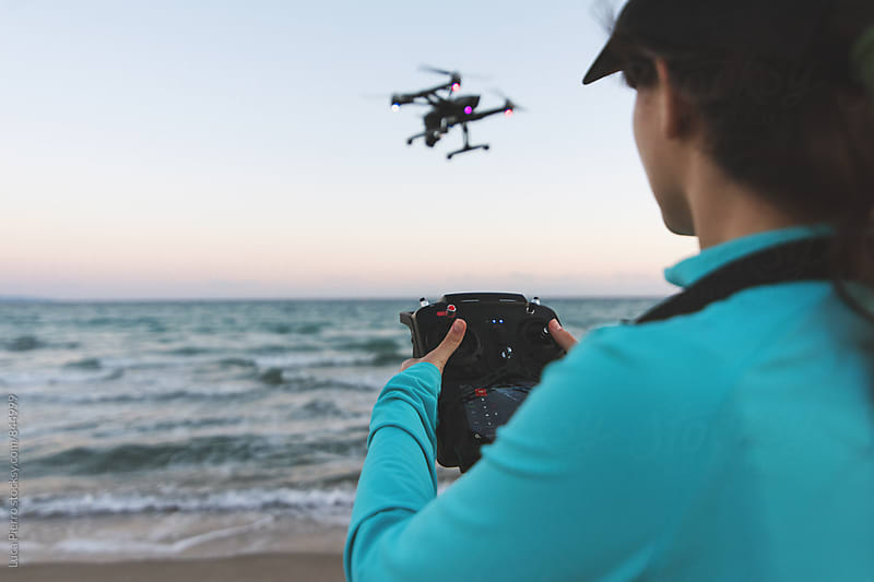 Active woman using a drone on the beach by Luca Pierro for Stocksy United