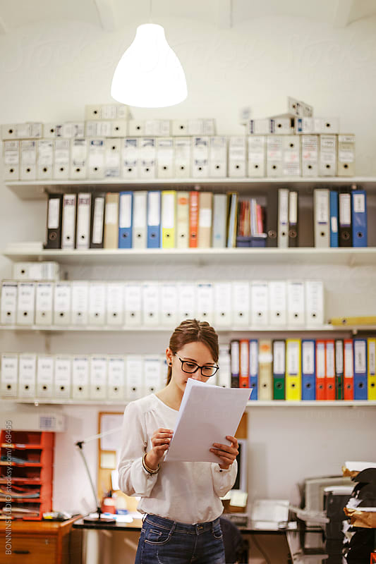 Young businesswoman reading documents at her office. by BONNINSTUDIO for Stocksy United