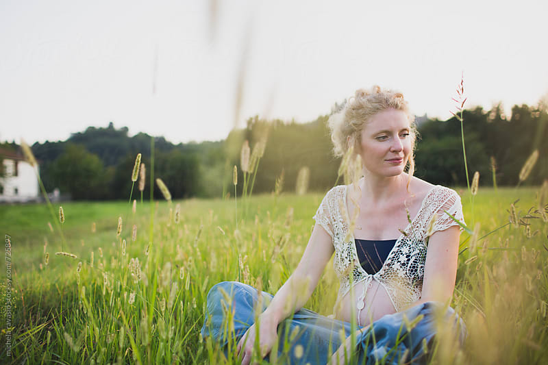 Serene pregnant woman relaxing on the grass by michela ravasio for Stocksy United