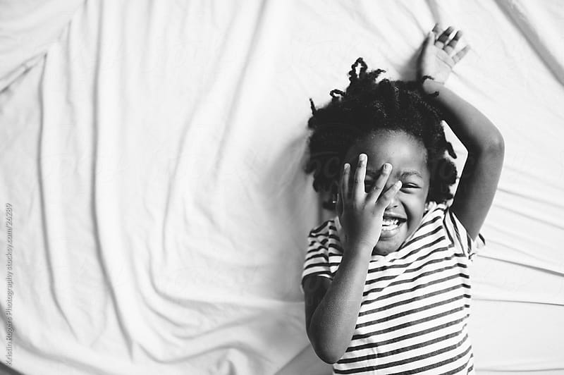 Little girl with hand over face as she laughs on bed by Kristin Rogers Photography for Stocksy United