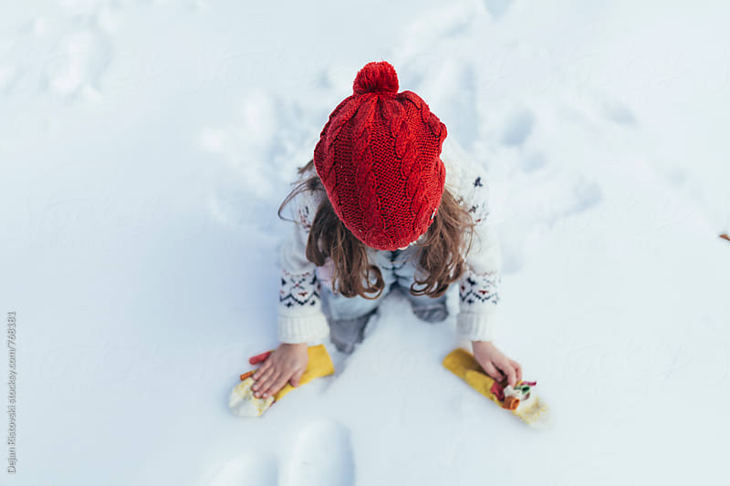 Child playing with snow outdoors by Dejan Ristovski for Stocksy United