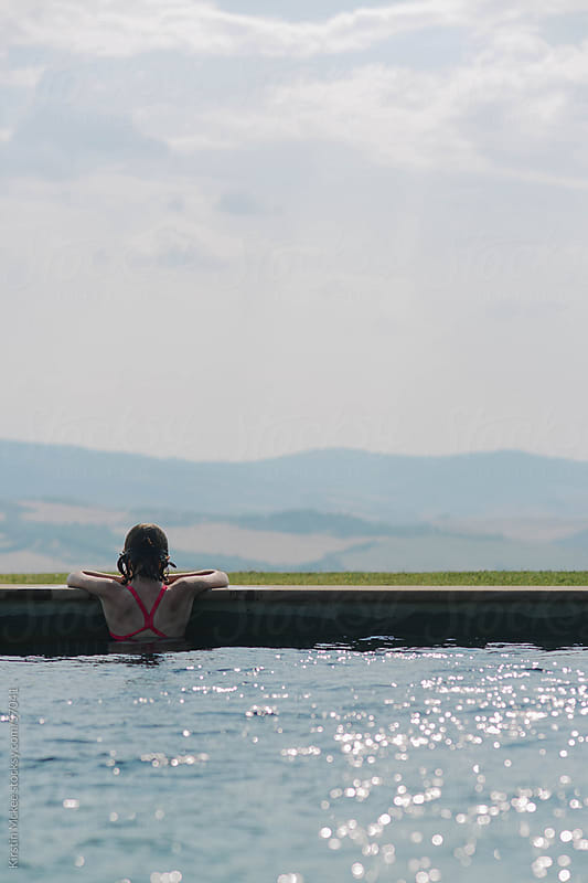 Girl enjoying  the view from a pool in Tuscany. by Kirstin Mckee for Stocksy United