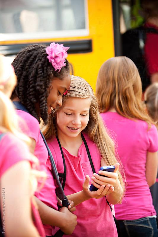 School Bus: Girl Shows Friend Funny Text by Sean Locke for Stocksy United