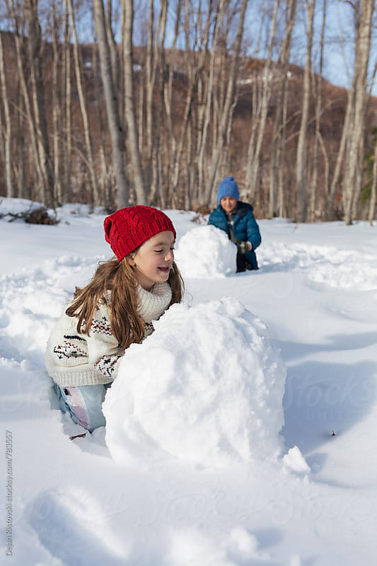Children rolling a big snowballs. by Dejan Ristovski for Stocksy United