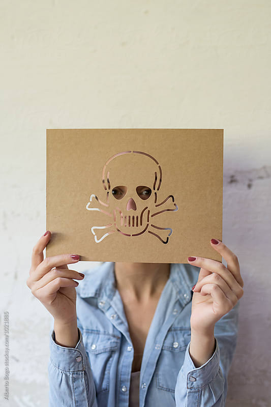 Unrecognizable person holding paperboard with carved skull by Alberto Bogo for Stocksy United