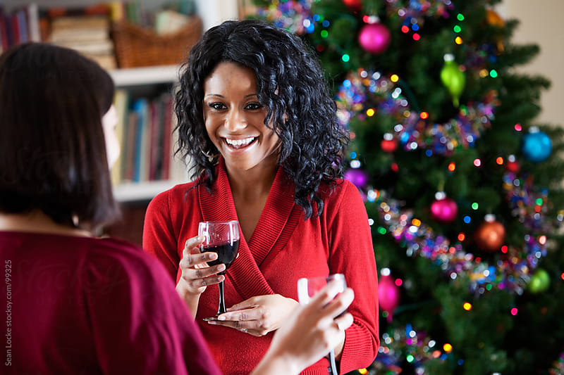 Christmas: Friends Talking Over Glass of Wine by Sean Locke for Stocksy United