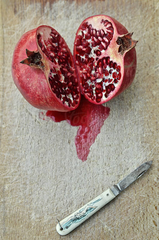 sliced pomegranate on plate by Marija Anicic for Stocksy United