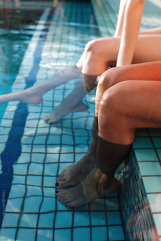 Women with their feet in a pool by Kayla Snell for Stocksy United