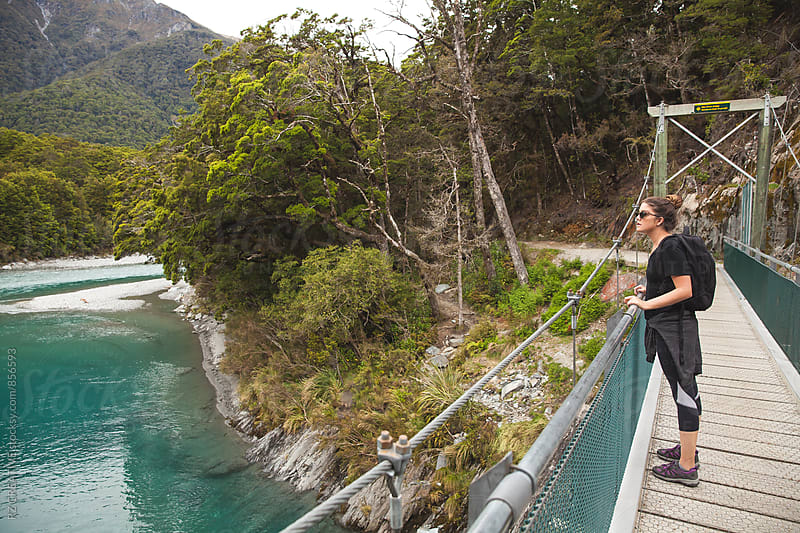Woman standing on a bridge at the Blue Pools Track in New Zealand. by Robert Zaleski for Stocksy United