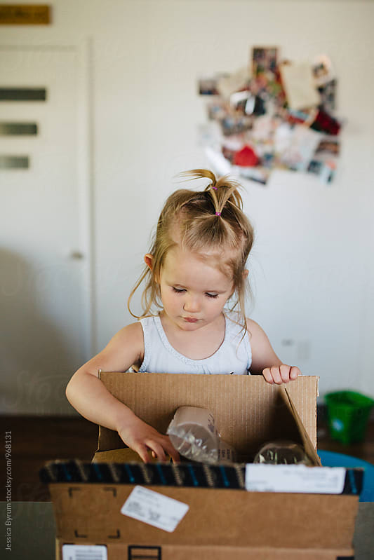 Toddler girl opening box by Jessica Byrum for Stocksy United