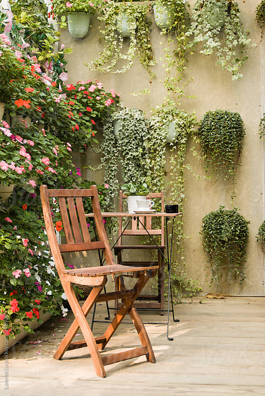 Wooden table and chair at garden with trailing and flower plants hanging on wall by Lawren Lu for Stocksy United