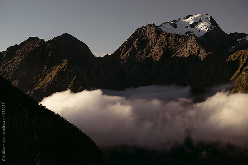 Clouds drifting through the Milford Sound valleys at sunset. by Christian McLeod Photography for Stocksy United