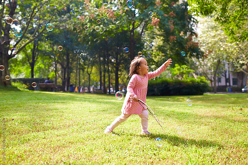 happy little asian girl after bubble in the sunshine park by Bo Bo for Stocksy United