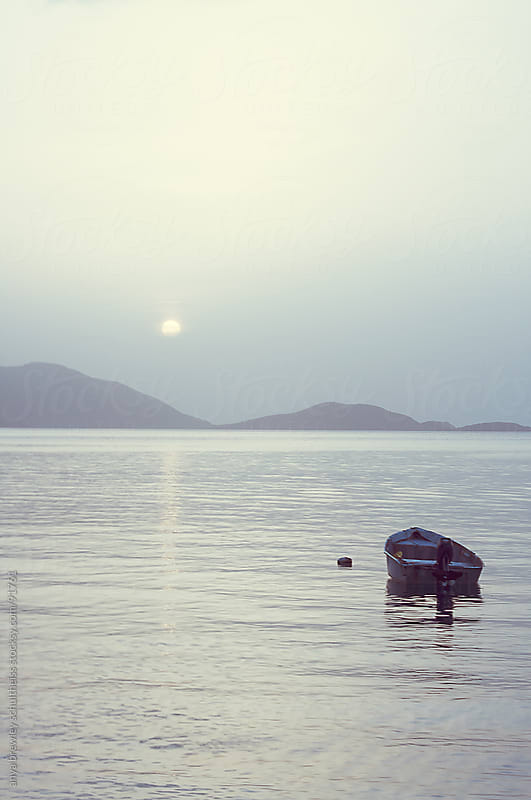 Single boat sitting on the sea at twilight by anya brewley schultheiss for Stocksy United