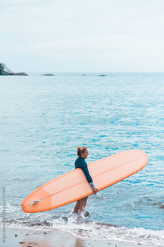 Young Woman Surfer Holding Orange Longboard and Standing in the Ocean by Briana Morrison for Stocksy United