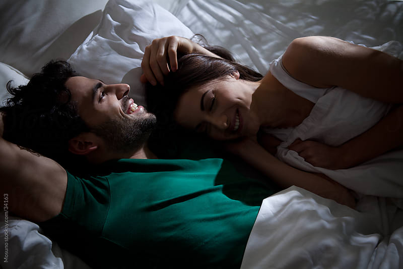 Young couple talking and laughing in bed before sleep. by Mosuno for Stocksy United