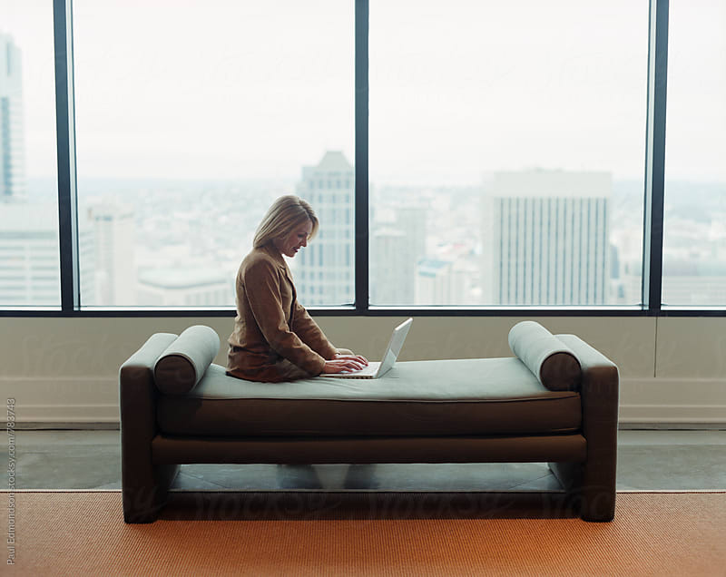 Female office executive sitting on couch and using laptop computer by Paul Edmondson for Stocksy United