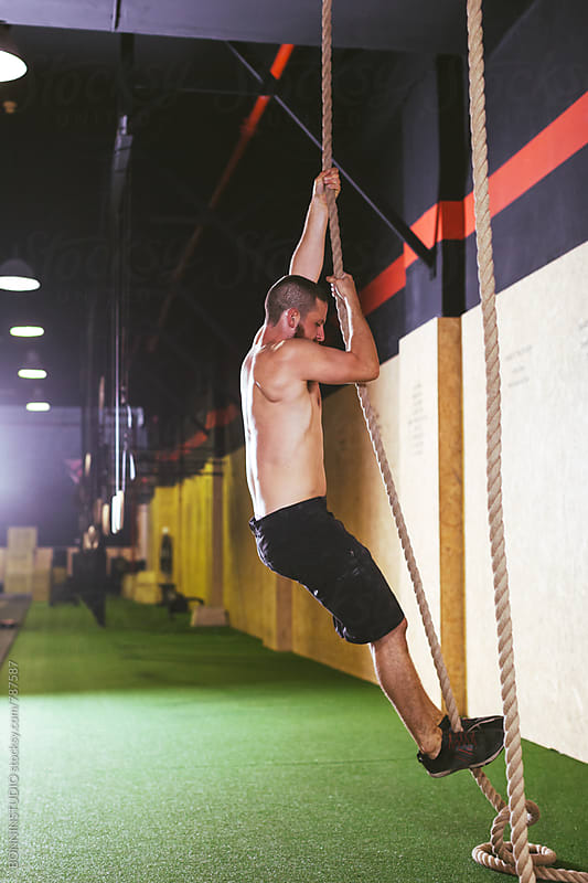 Side view of a man climbing a rope in a gym. by BONNINSTUDIO for Stocksy United