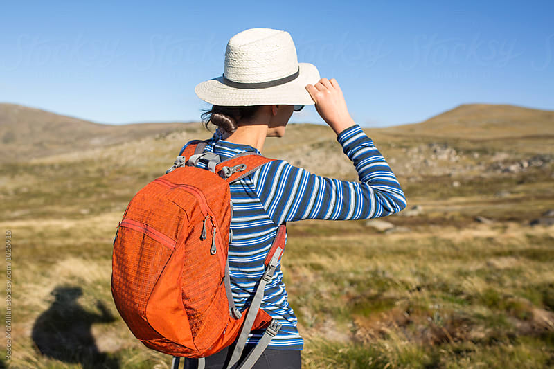 A hiker adjusts her hat by Reece McMillan for Stocksy United