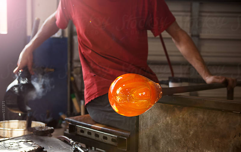 Glass: Male Artist Cools Shaping Block In Water Before Reuse by Sean Locke for Stocksy United