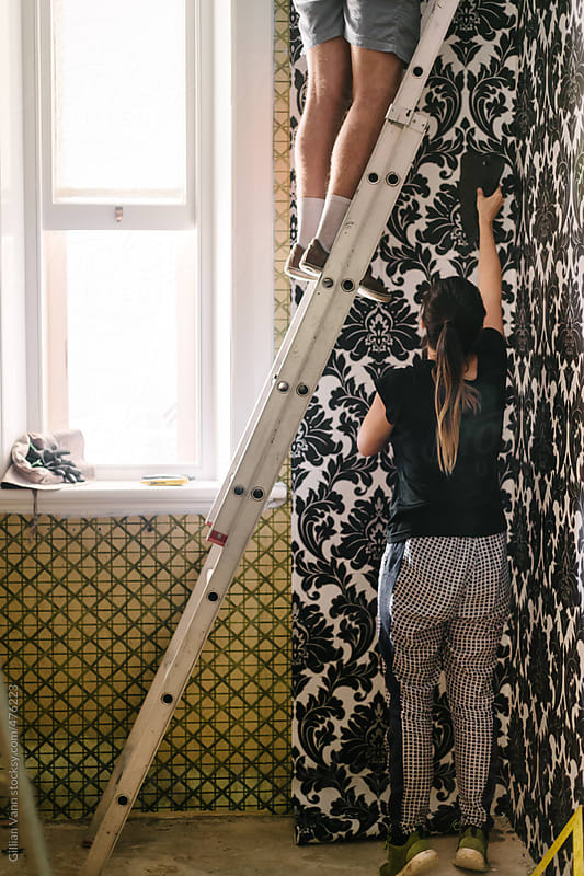 wallpapering day in the House Renovation project, a couple work together to hang wallpaper by Gillian Vann for Stocksy United