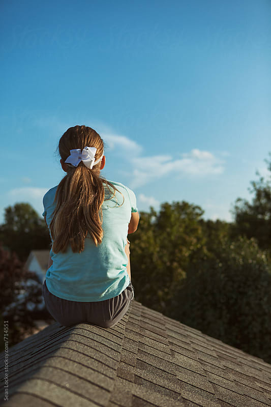 Roof: Rear View Of Teen Girl Sitting On The Rooftop Of A House by Sean Locke for Stocksy United