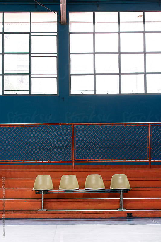 Empty seats in the bleacher section of an indoor gymnasium by Lawrence del Mundo for Stocksy United