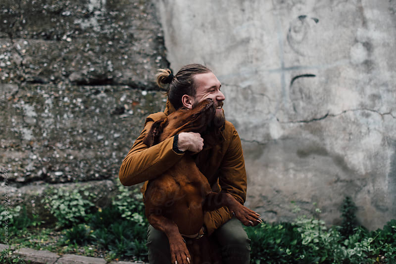 Portrait of man playing with his dog by Boris Jovanovic for Stocksy United