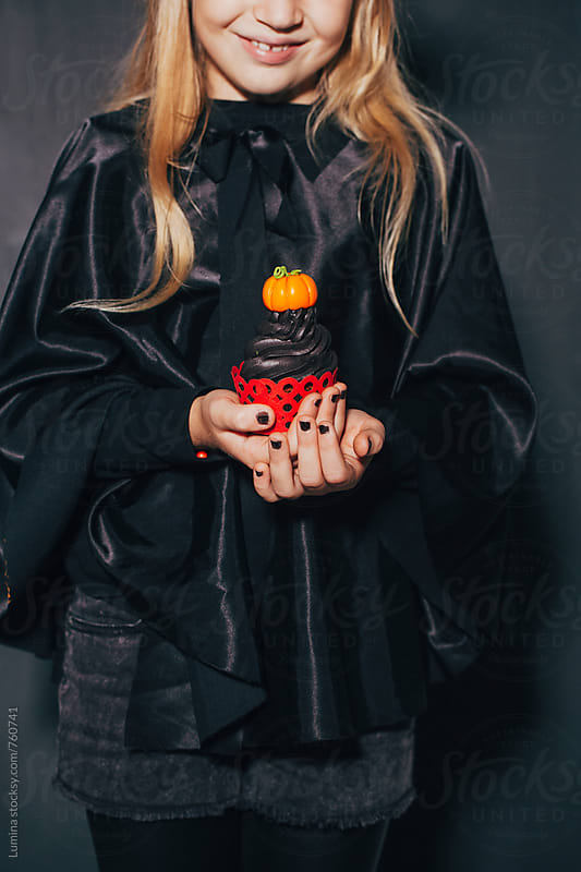 Girl in a Witch Costume Holding a Halloween Cupcake by Lumina for Stocksy United