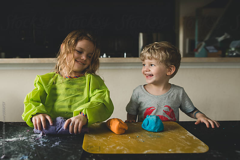 children laughing and smiling while making dough  by Courtney Rust for Stocksy United