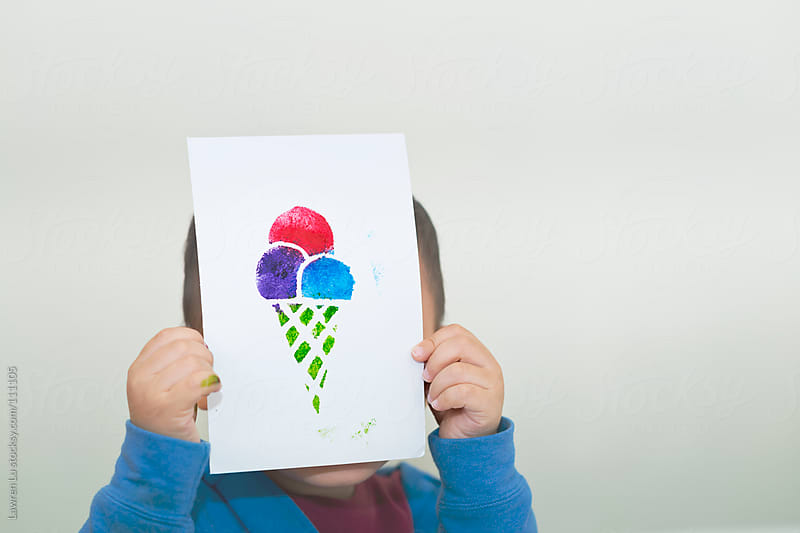 Child display his painting, an ice-cream on paper by Lawren Lu for Stocksy United