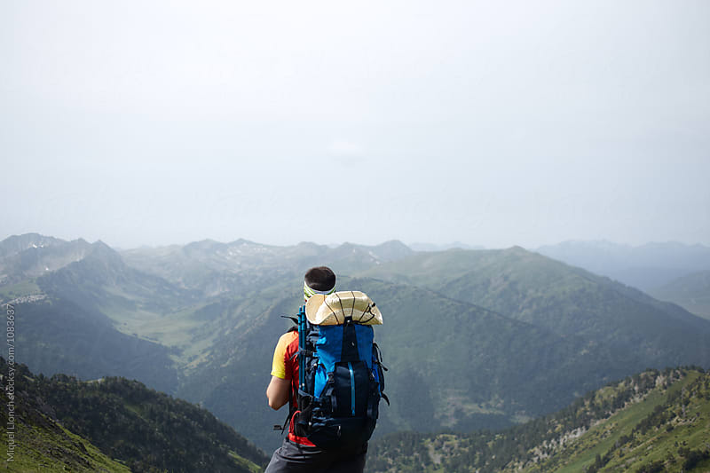 Backpacker contemplating the mountain landscape by Miquel Llonch for Stocksy United