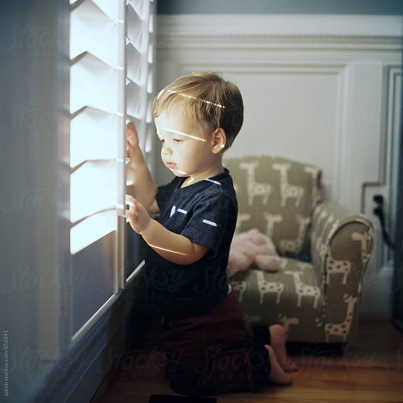 Cute young boy playing with window blinds by Jakob for Stocksy United