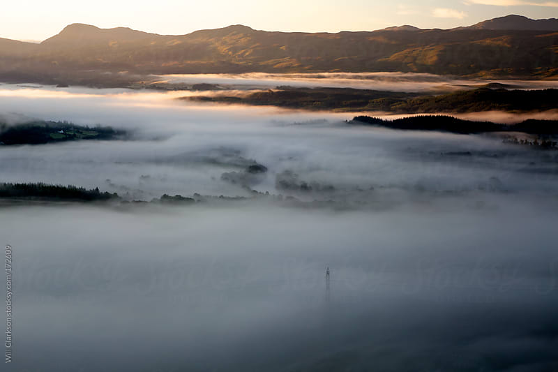 Landscape of the end of a misty glen in Scotland and sunrise by Will Clarkson for Stocksy United