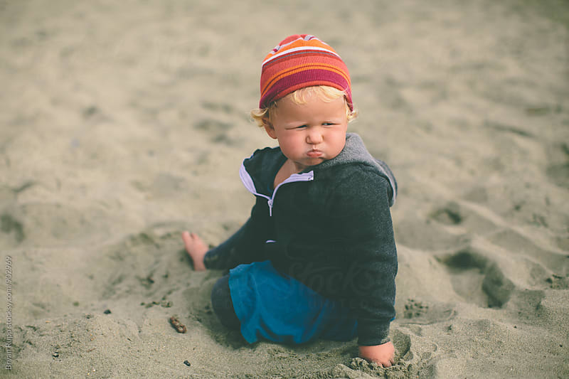 Little Girl Making a Funny Face on the Beach by Bryan Rupp for Stocksy United