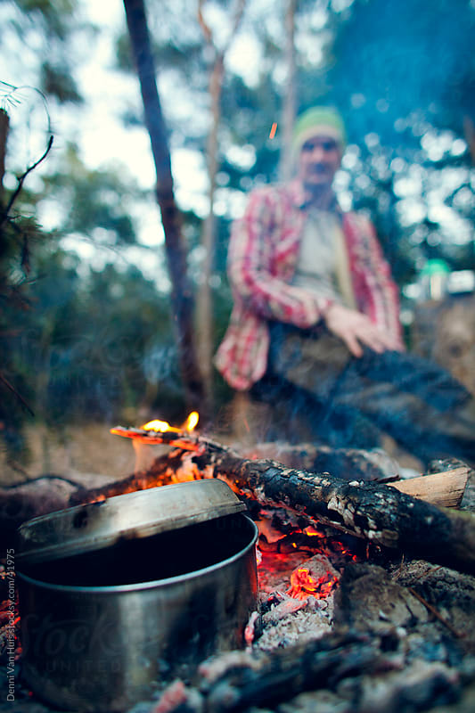 Young man sitting next to a campfire cooking dinner by Denni Van Huis for Stocksy United