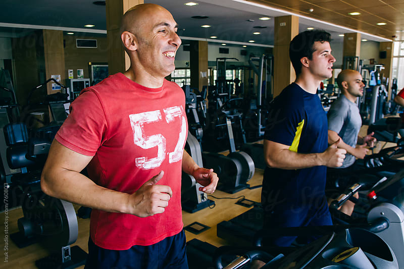Three men running on a treadmill in a gym by Inuk Studio for Stocksy United