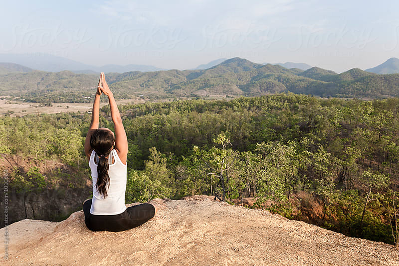 Woman in yoga position overlooking mountain landscape by Soren Egeberg for Stocksy United