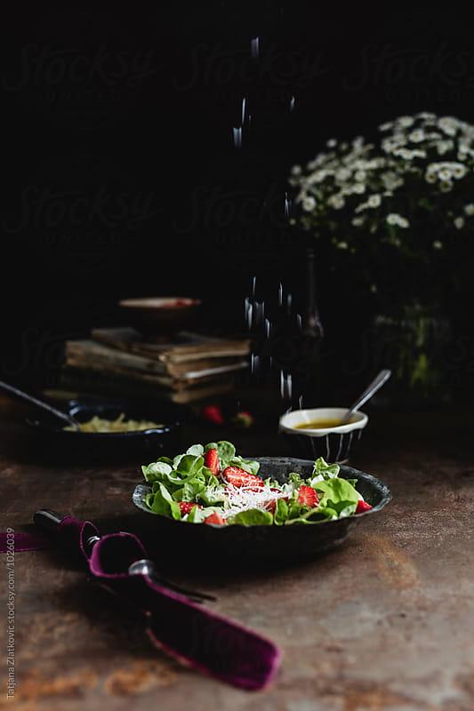 Sprinkling parmesan on strawberry salad by Tatjana Zlatkovic for Stocksy United