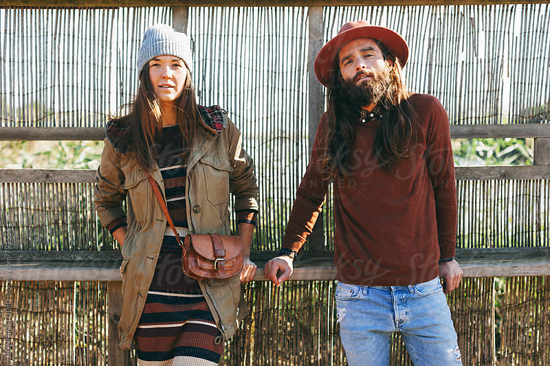 Portrait of hipster couple standing on a wetland. by BONNINSTUDIO for Stocksy United