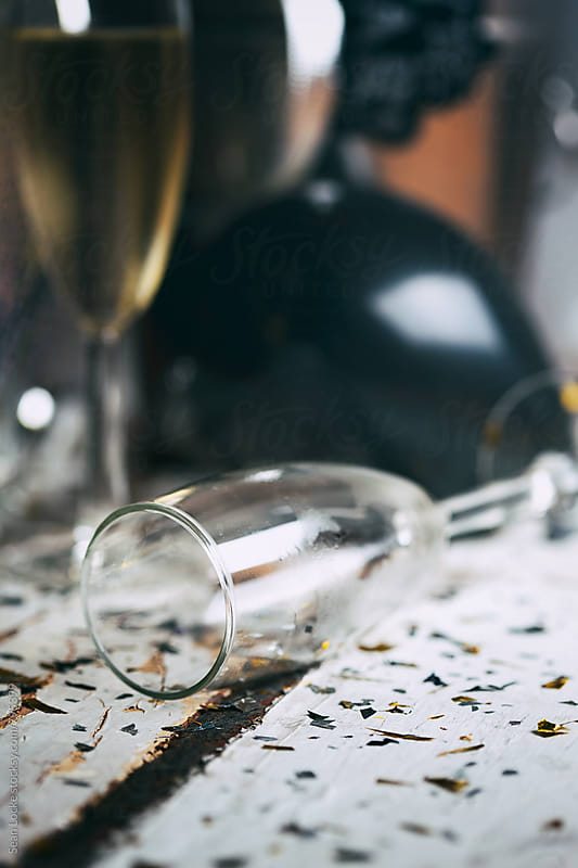 NYE: Empty Champagne Flute Lays On Rustic Table Top With Confetti by Sean Locke for Stocksy United