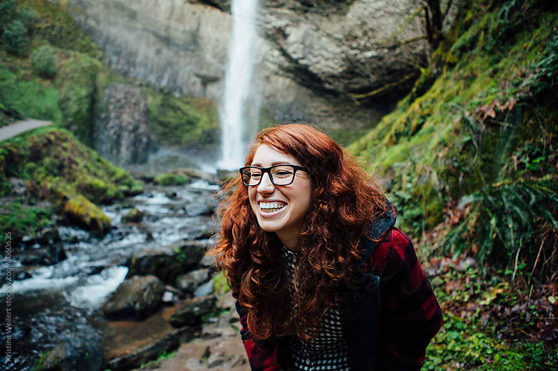 Beautiful woman smiling on a hike near a waterfall by Kristine Weilert for Stocksy United