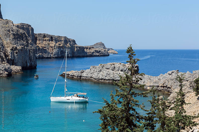 Sailing boat moored in a rocky cove. by Paul Phillips for Stocksy United