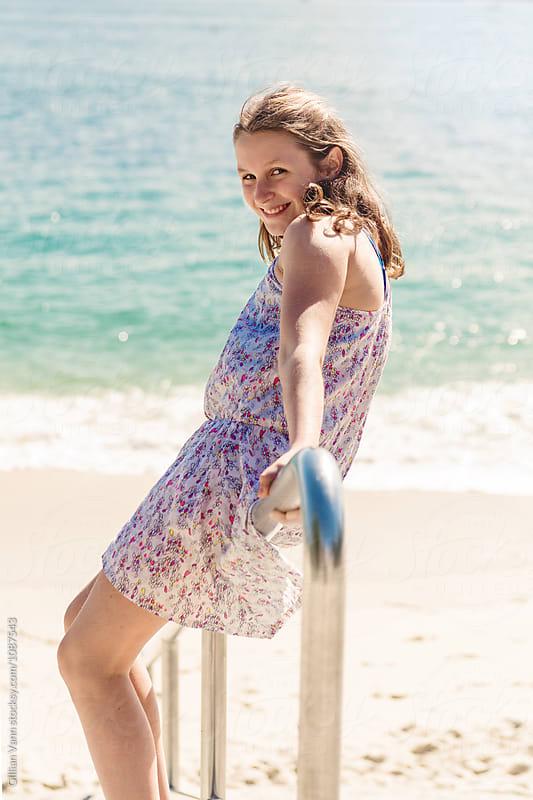 teen girl sliding down stair rail at the beach by Gillian Vann for Stocksy United