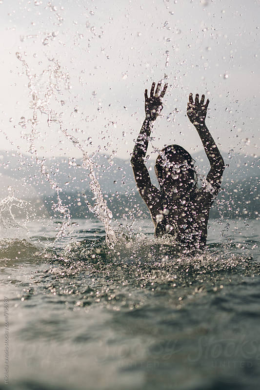 Woman splashes in the lake at sunset by michela ravasio for Stocksy United