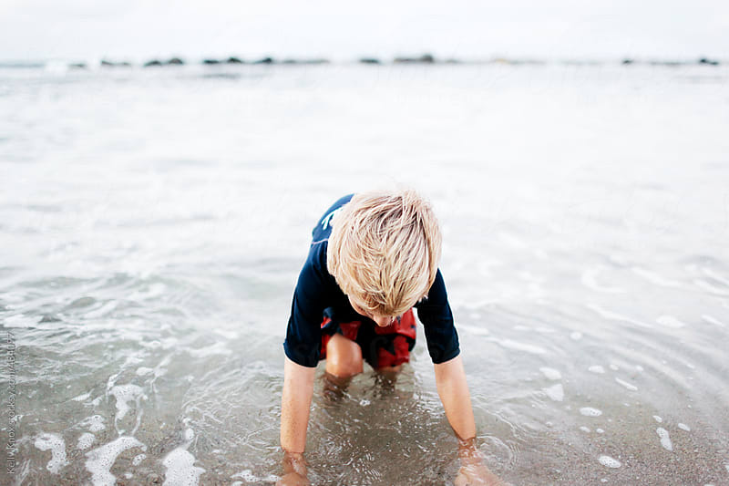 young child playing in the ocean by Kelly Knox for Stocksy United