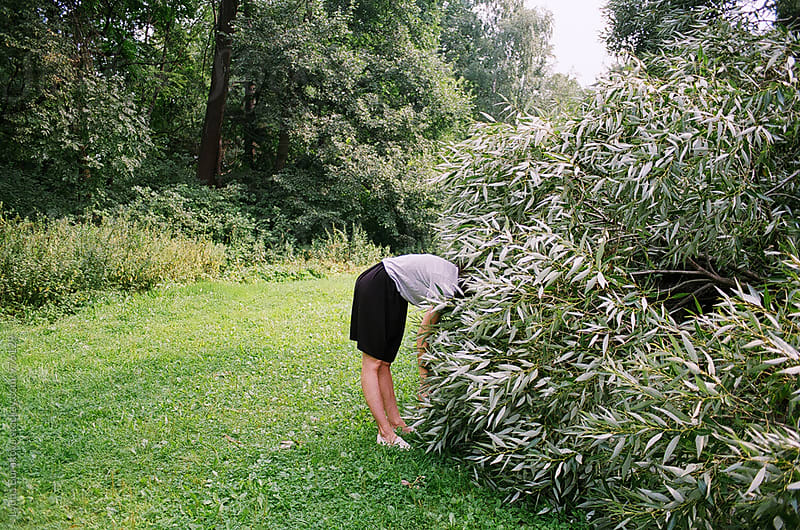 Young woman hide her head in a bush by Liubov Burakova for Stocksy United